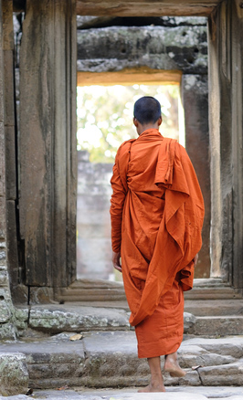 Buddhistischer Mönch passiert Torbogen, Banteay Kdei Tempel in Angkor, Kambodscha