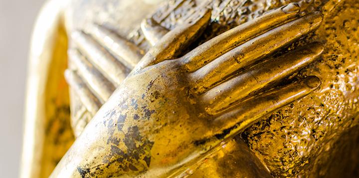 Goldene-Buddhastatue-mit-auf-der-Brust-ruhenden-Haenden